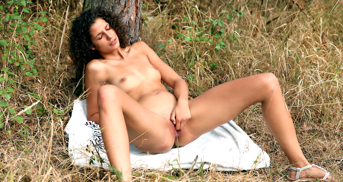 Brunette masturbating in the woods